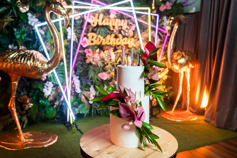 Flamingo themed birthday party ideas for girls birthday party decorations. Neon signage, artificial grass wall table runner, flamingo party props, tropical flower arrangement and tropical birthday cake.