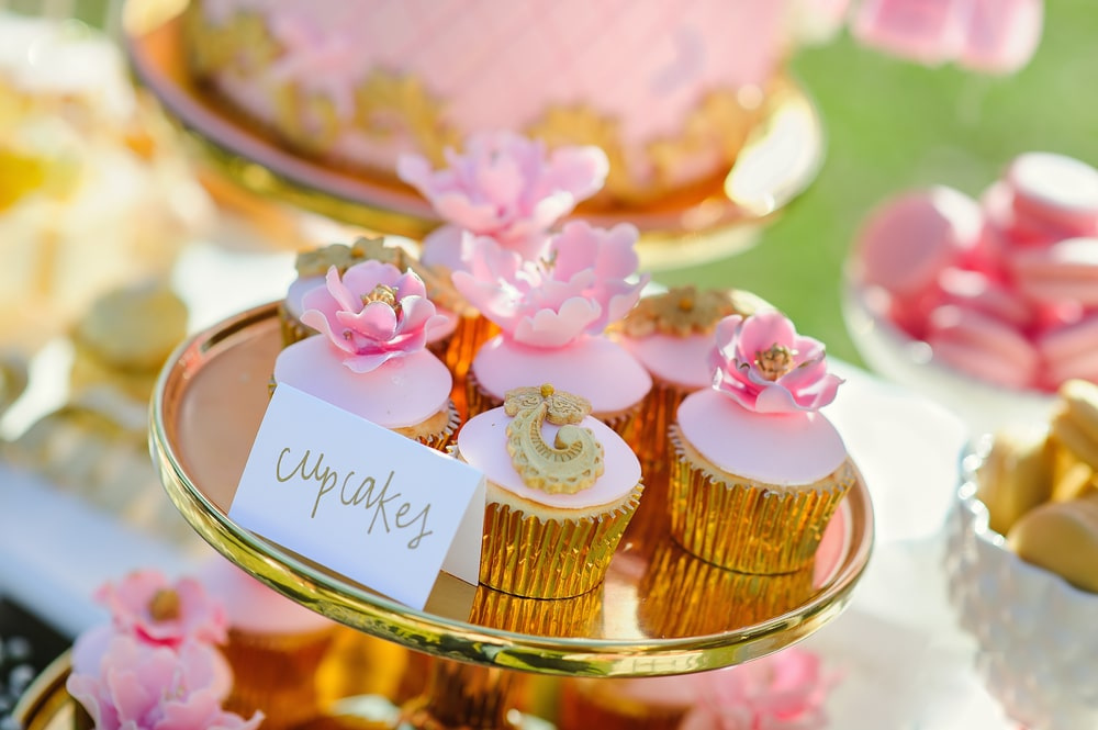 Baby shower pink dessert table details with pink and white flower and butterfly cupcakes on a dessert table for baby shower and girls birthday party decor ideas.