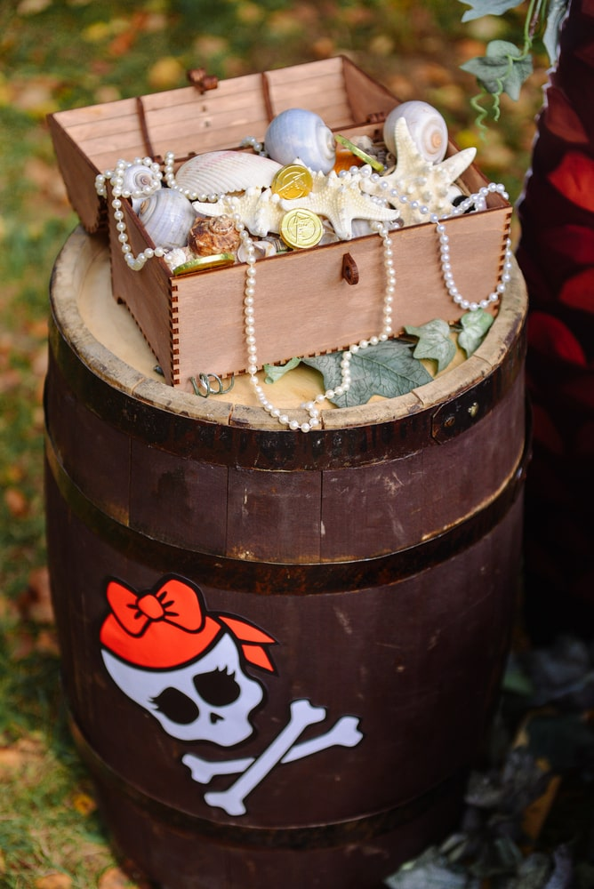 Pirate themed children's party decorations pirate barrel with pirate treasure chest filled with gold coins and jewels. Pirate flag symbol party decorations.