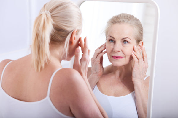 Woman Looking in Mirror with Hands Running Over Face