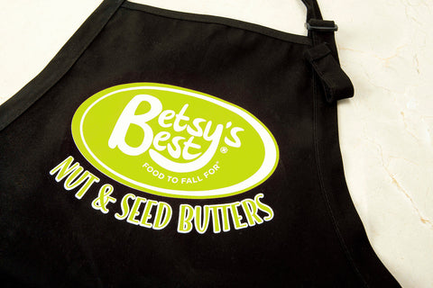 A Betsy's Best Gourmet Nut and seed Butter Apron with a green logo on a black material