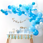 Blue balloon arch above a table with party decorations