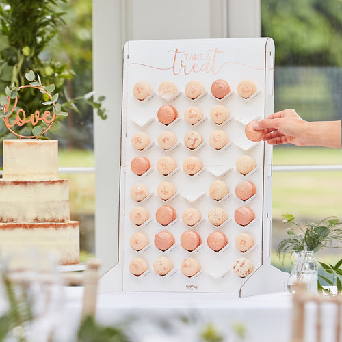 "Macaron wall with ""Take a treat"" printed on the top part, a hand is taking a macaron."