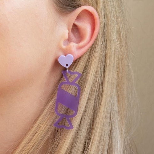 Purple acrylic wrapped candy earring on ear.