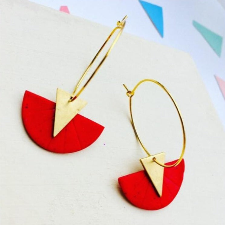 Closeup of a handmade polymer clay hoop earrings featuring a geometric circle design in red, complemented with brass triangles.