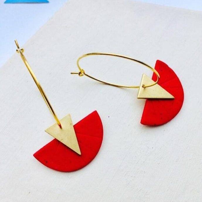 Side shot of a handmade polymer clay hoop earrings featuring a geometric circle design in red, complemented with brass triangles.