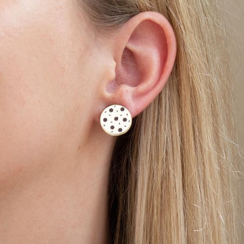 Gold acrylic chocolate chip cookie earring on ear.