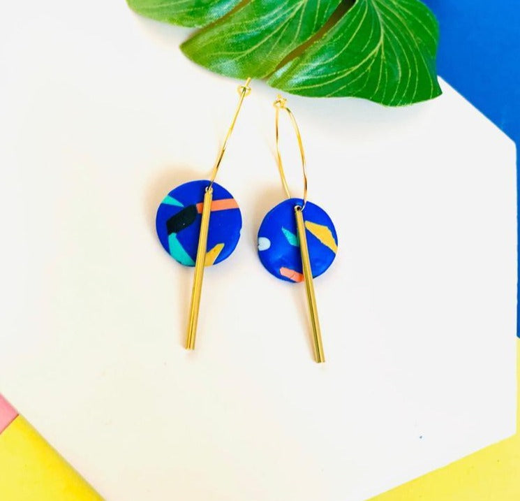 Dangle earrings handmade using polymer clay in a fun colorful 80s inspired pattern on a royal blue background, complemented with brass bar findings.