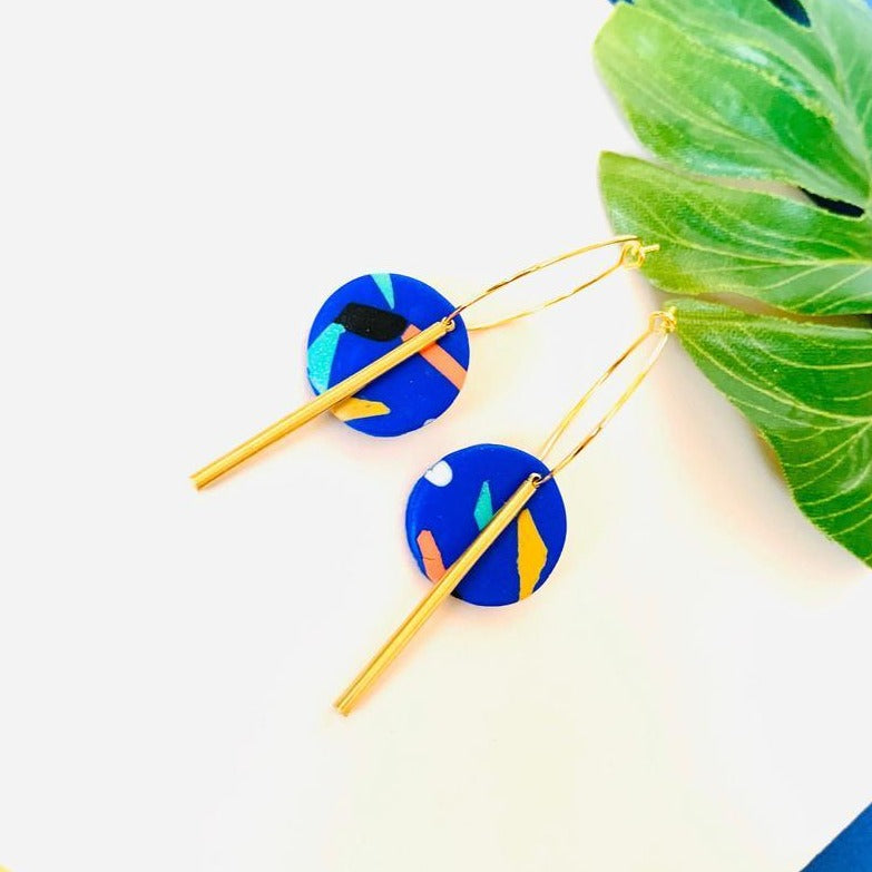 Front shot of dangle earrings handmade using polymer clay in a fun colorful 80s inspired pattern on a royal blue background, complemented with brass bar findings.