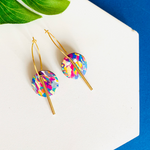 Far front shot of multi-colored hoop earrings with gold accessories