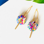 Front shot of multi-colored hoop earrings with gold accessories
