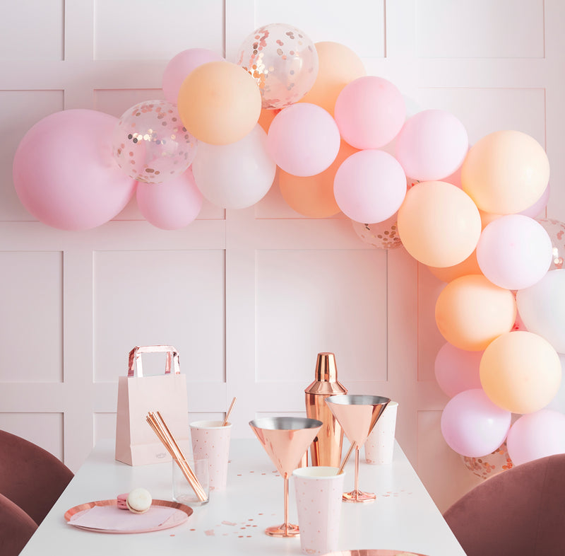 Peach/pink balloon arch above table with bronce martini cups