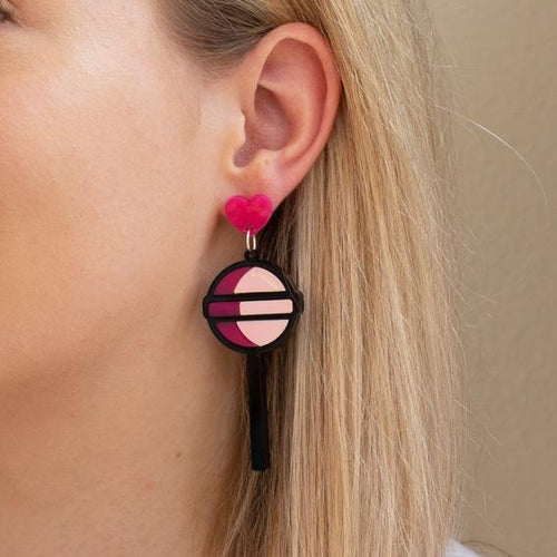 Acrylic lollipop earring on ear.