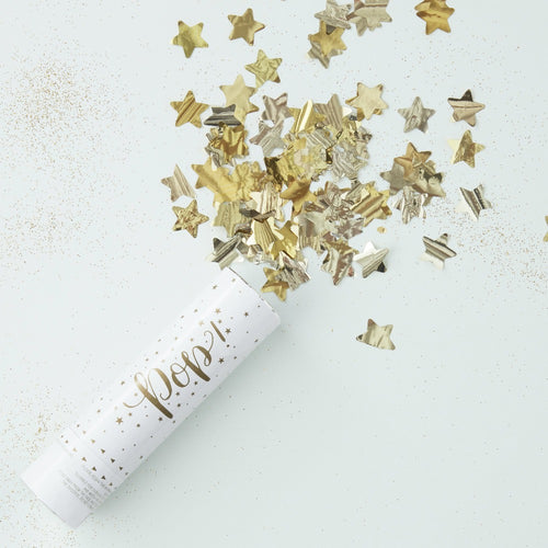 Pop! white conffetti cannon with gold star shaped conffetti flakes on white background.