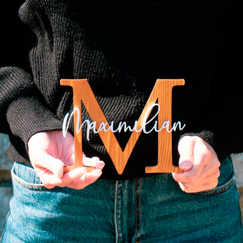 "Person holding wooden ""M"" monogram sign with ""Maximilian"" on top."