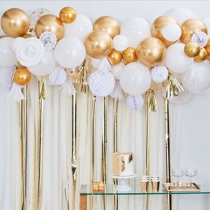 Gold and white balloons with white fan garland as decoration in white room with party decorations