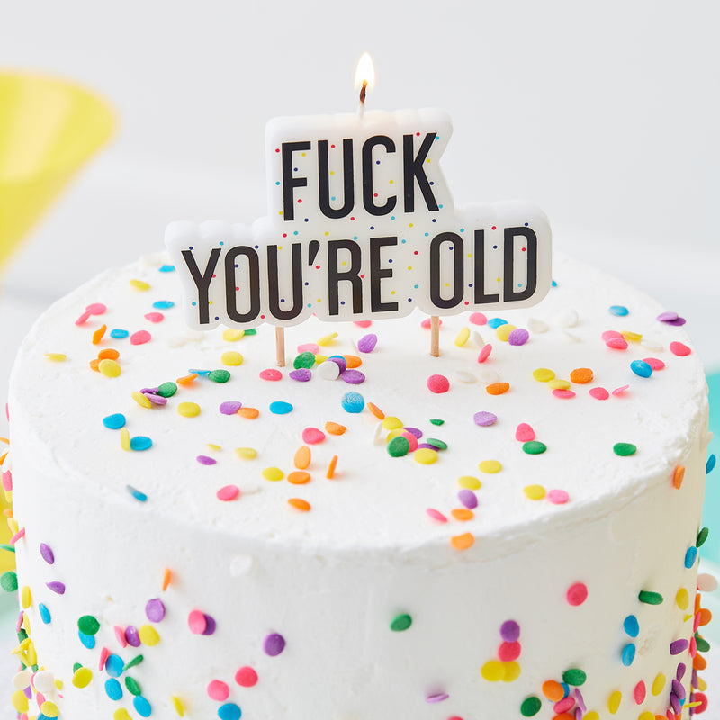"""Fuck you're old"" birthday candle on white cake with sprinkles"