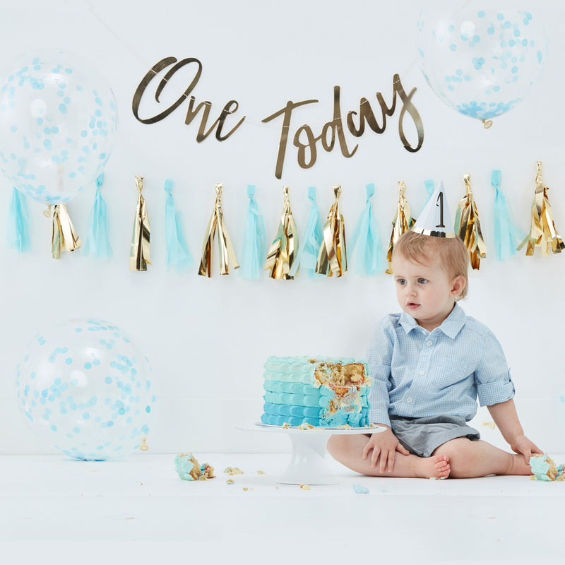 Baby boy sitting in front of blue cake surrounded by blue and gold birthday decoration
