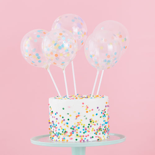Pastel confetti balloon cake toppers on cake with confetti sprinkles