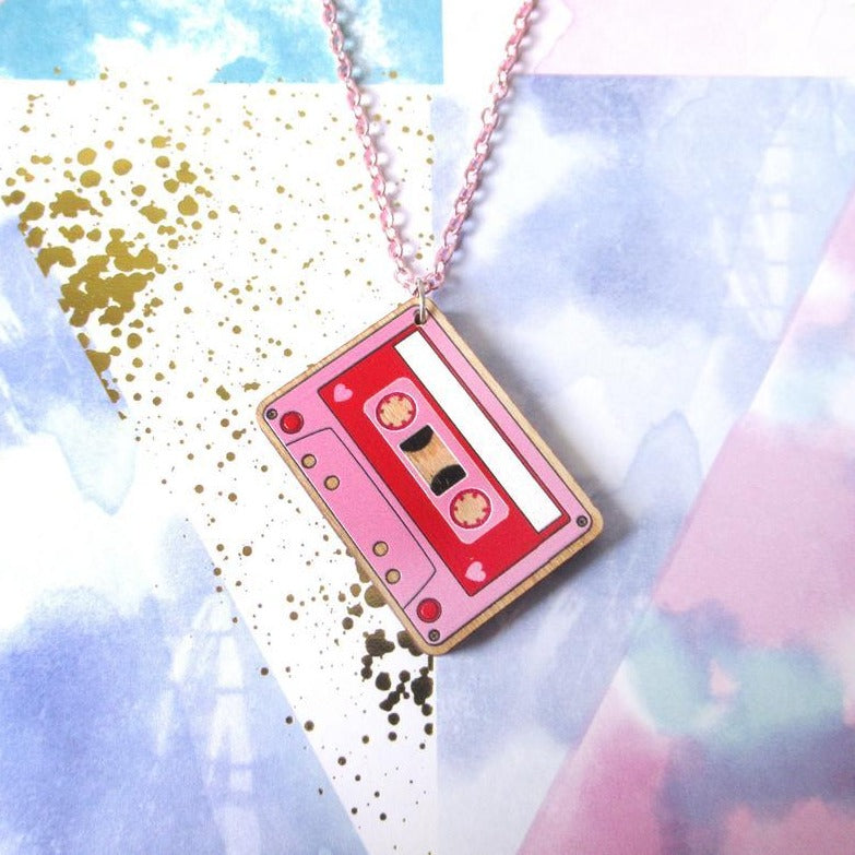 Front shot of pink and red wooden cassette medallion with pink chain on a multicolored background