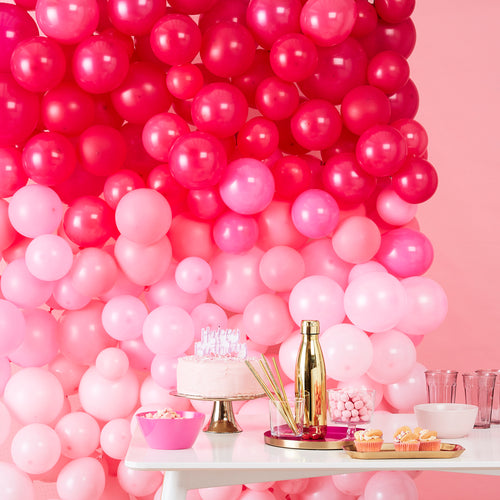 Pink ombre balloon wall behind table with party decorations and cake