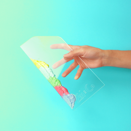 Transparent acrylic cake scraper with colorful cream being held sideways