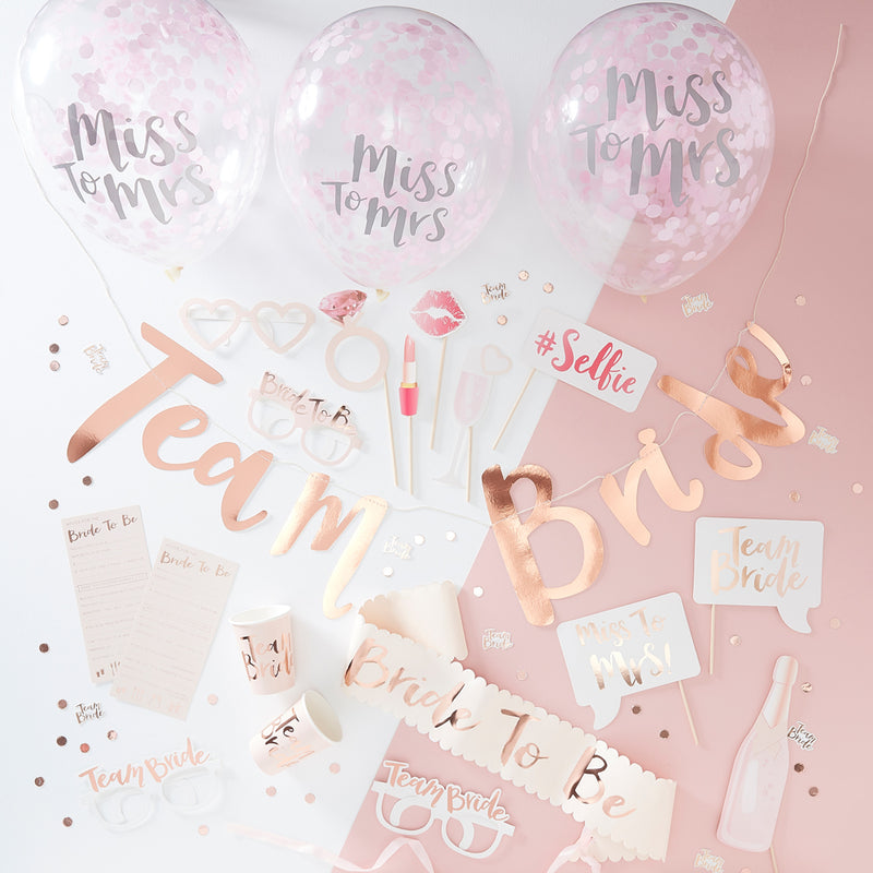 Diverse hen party decorations on a white and pink background