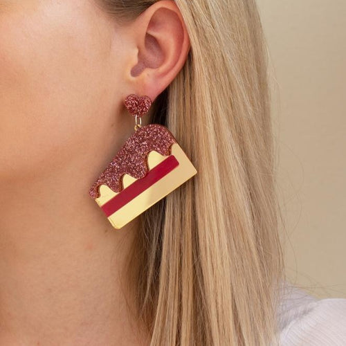 gold and red acrylic cake slice earrings on ear