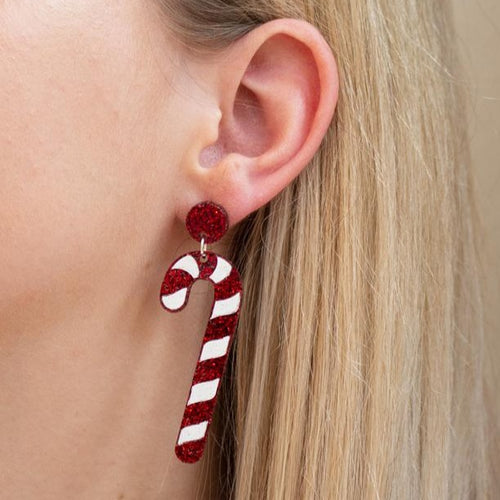 White and glitter red acrylic candy cane earring on ear.