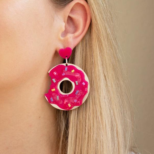 Pink and gold acrylic sprinkled donut earring with a bite missing on ear.