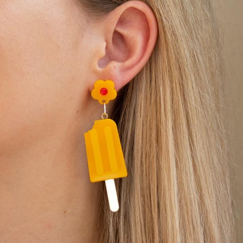 Yellow and gold acrylic ice pop earring on ear.