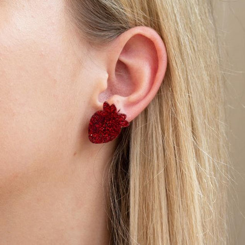Red glitter acrylic strawberry earring on ear.