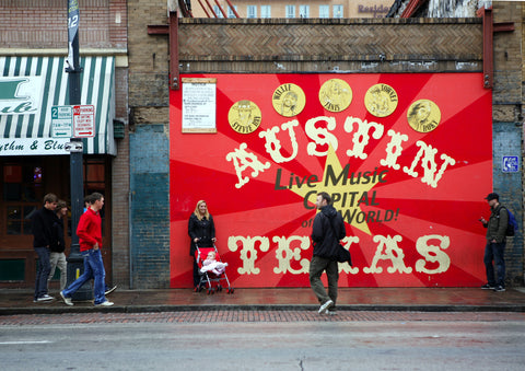 brick wall in downtown austin texas with writing on red background that says austin texas live music capital of the world man taking picture of woman with a baby in a stroller in front of the painted wall other people walking by watching