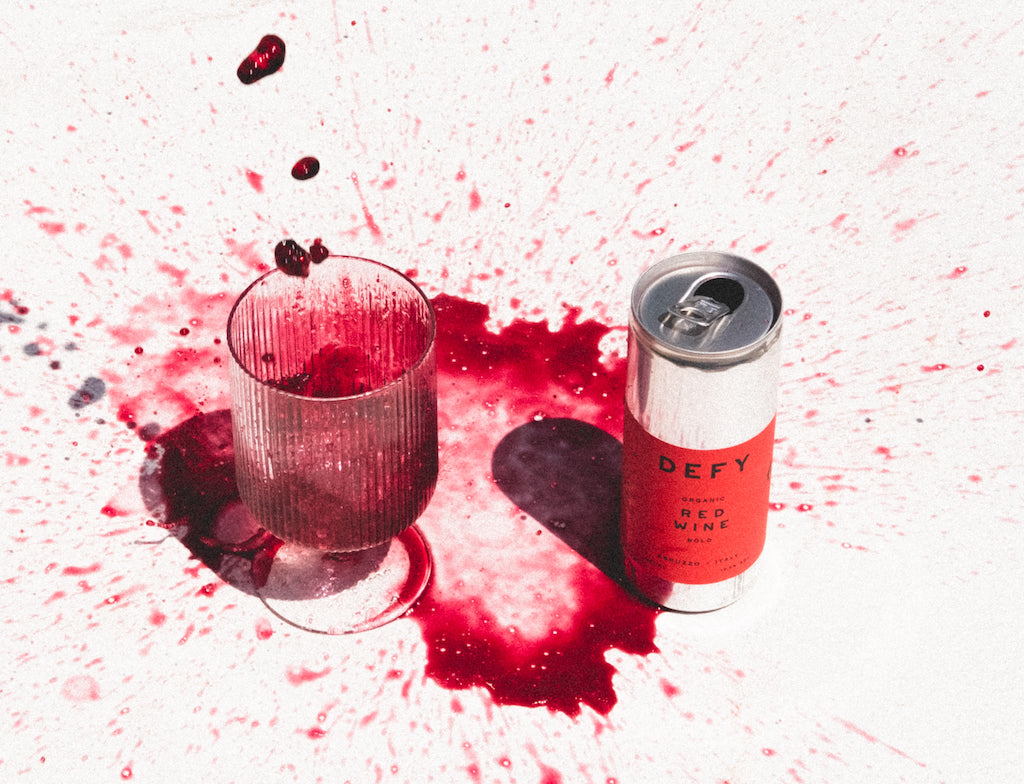 A glass of DEFY's vegan, Organic Italian Red Wine being poured and splashed all over a white, stone table, sat next to a can of the wine.