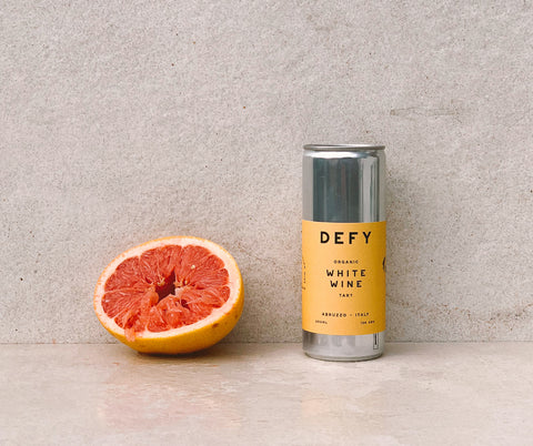 Can of DEFY white wine next to half a squeezed grapefruit