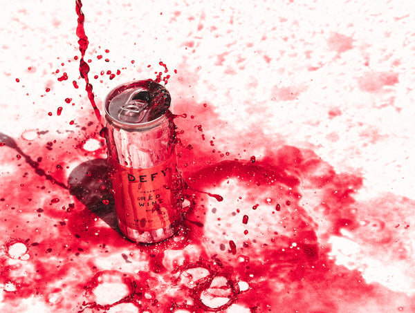 Can of DEFY vegan, Organic Italian Red Wine with the wine splashing all over it.