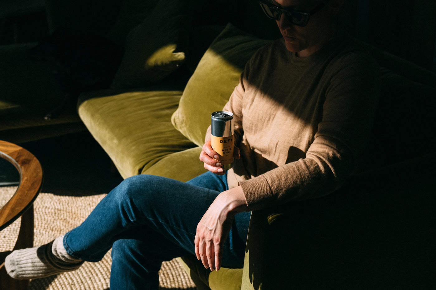 Em, sat on a sofa is strong sunlight, drinking a can of Organic Italian White Wine from DEFY