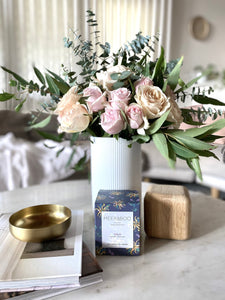 A scented candle in gift box, next to fresh flowers on a marble table top, photographed in a living room.