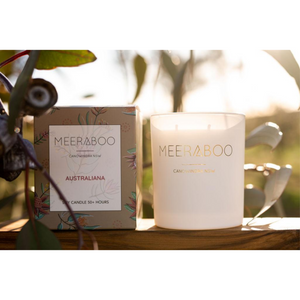 A scented candle in white jar with gold Meeraboo branding, next to a floral gift box in the sunlight.