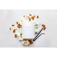 Load image into Gallery viewer, A scented candle in white jar from Meeraboo brand, surrounded by almonds, vanilla beans and white flowers.