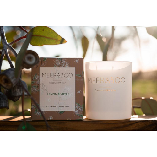 Meeraboo soy candle lemon myrtle limited edition gift box and Meeraboo soy candle in white jar, sitting in the sun surrounded by tree leaves.