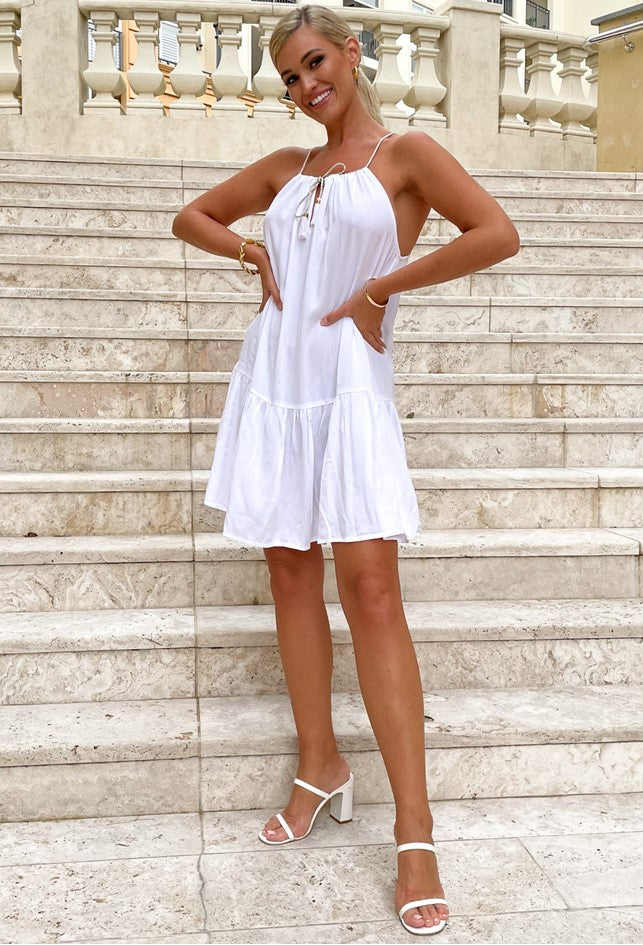 White Cotton Mini Holiday Dress named Toulouse by Lindsey Brown, sitting just above the knee with a pretty gold tie neckline and white tassels