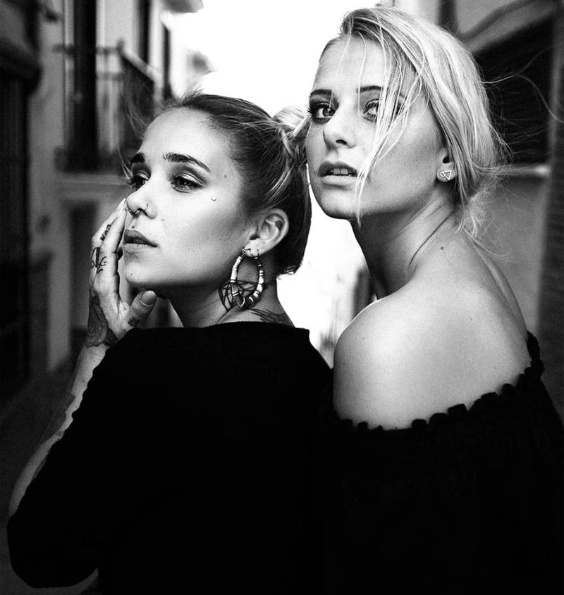 black and white portrait of two young women in Mallorca. Blonde and black hair. For a photo-magazine.