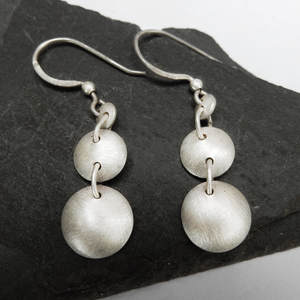 Open image in slideshow, Silver triple silver disc drop earrings with a brushed finish.