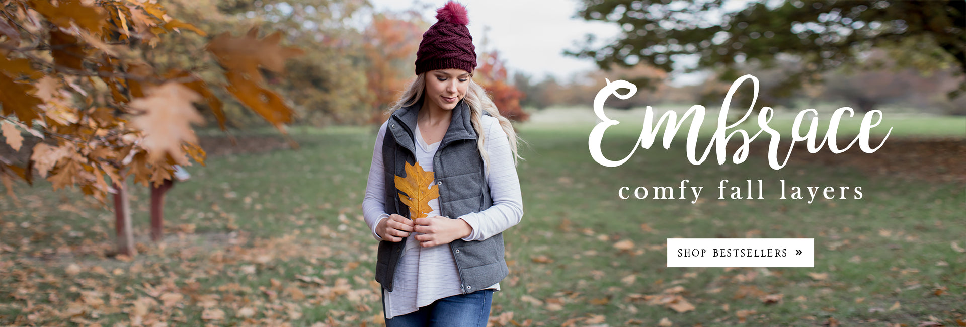 Embrace Comfy Fall Layers - Woman in vest holding leaf