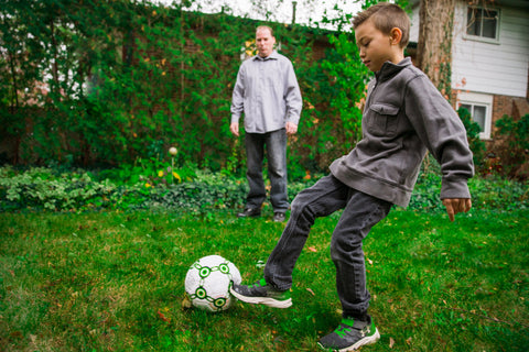 A father and son playing soccer