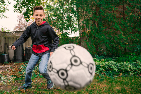 A kid catching a soccer ball