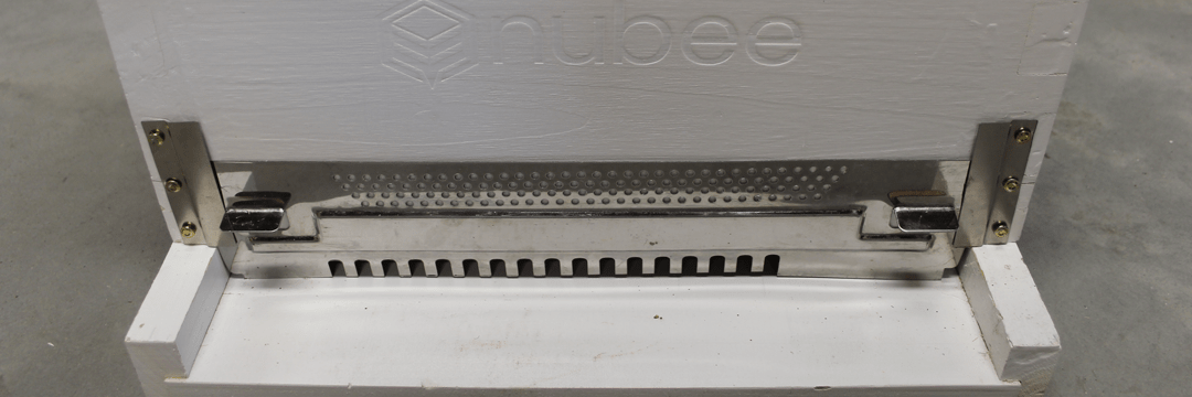 Close up of white NuBee Hive's entrance that has a metal entrance blocker in front of it. Properly installed.