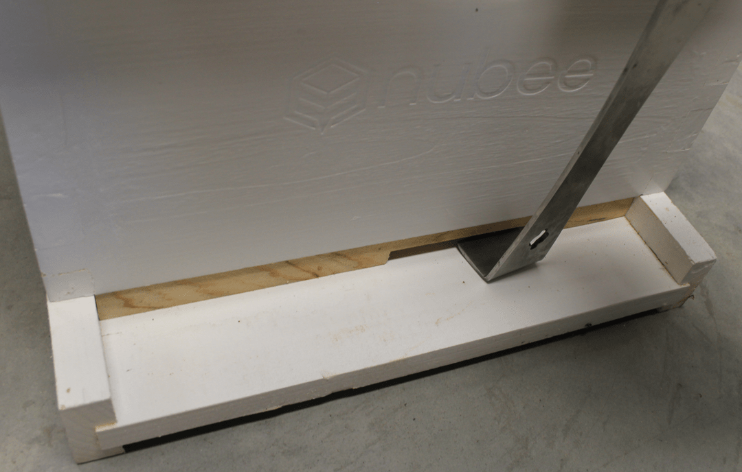 A white NuBee brood box is sitting on its solid bottom board. A wedged entrance reducer is being pryed out by a hive tool