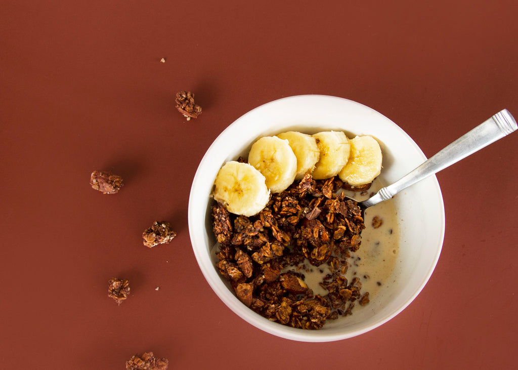 Organic superfood chocolate granola in bowl of milk and bananas
